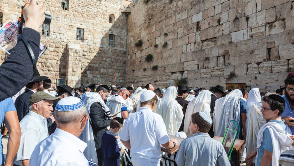 Jerusalem, Israel  - October 12, 2014: Crowd of faithful Jews wearing prayer shawls. Morning autumn Sukkot. The area in front of Western Wall of  Temple filled with people